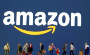 Small toy figures are seen in front of diplayed Amazon logo